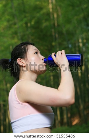 young asian woman holding water outside