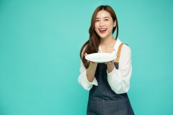 Young Asian woman in apron standing and holding empty white plate or dish isolated on green background