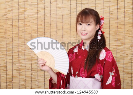 Young asian woman in traditional clothes of kimono with paper fan, on bamboo blind background