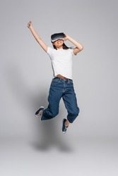 young asian woman in white t-shirt, jeans and gumshoes jumping with raised hand while using vr headset on grey