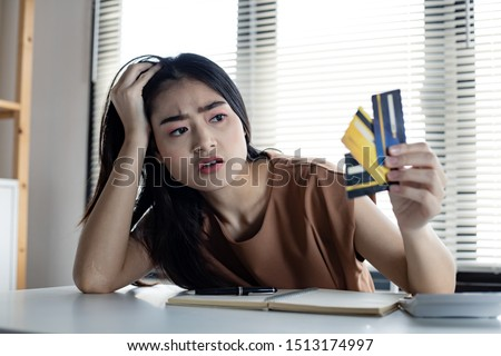 Young Asian woman is stressed and overthink by debt from many credit cards. Concept of financial problem. Women figured out a way out of debt at hand. Tired of getting into credit card debt.