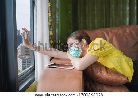 Young asian woman isolating at home with tablet on the sofa in the living room. She is bored because stay at home campaign for coronavirus prevention. Photo stock ©