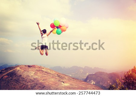 young asian woman jumping on mountain peak cliff edge with colored balloons  #257744473