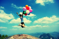young asian woman jumping on mountain peak rock with colored balloons
