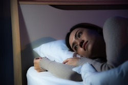 Young Asian woman lay down on bed and suffering insomnia sleepless in bedroom at night time. Nightmare sick