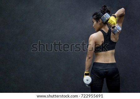 Young Asian woman lifting dumbbell in weight training fitness gym, sport exercise and muscular build, healthy lifestyle