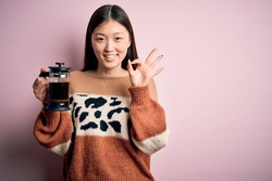 Young asian woman making a glass of coffe using french press coffee maker over pink background doing ok sign with fingers, excellent symbol