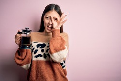 Young asian woman making a glass of coffe using french press coffee maker over pink background with happy face smiling doing ok sign with hand on eye looking through fingers