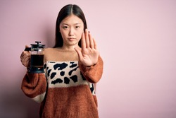 Young asian woman making a glass of coffe using french press coffee maker over pink background with open hand doing stop sign with serious and confident expression, defense gesture