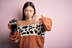 Young asian woman making a glass of coffe using french press coffee maker over pink background with angry face, negative sign showing dislike with thumbs down, rejection concept