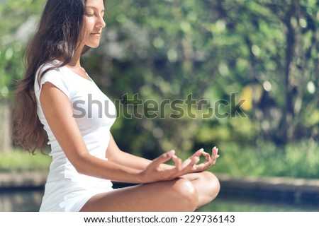 Young Asian woman meditating in a garden sitting i the Lotus position with her eyes closed and a tranquil expression with closed eyes