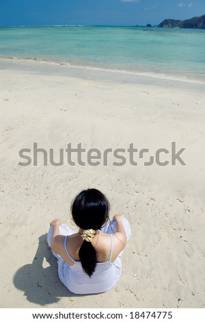 young asian woman meditating on the beach