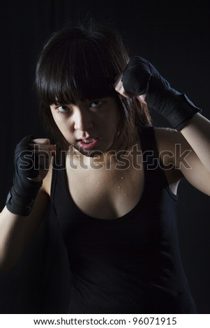 Young Asian Woman Muay Thai fighter in defensive position. On black background