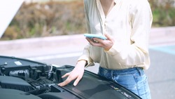 Young asian woman opening bonnet of vehicle. Road service. Roadside assistance.