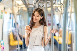 Young Asian woman passenger listening music via smart mobile phone in subway train when traveling in big city,japanese,chinese,Korean lifestyle and daily life, commuter and transportation concept