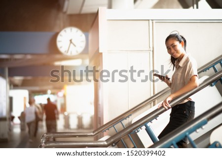 Young asian woman passenger uses a mobile phone and a smart phone to walk down the stairs in the train station. While traveling home