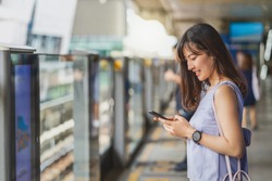 Young Asian woman passenger using social network via smart mobile phone in subway train when traveling in big city,japanese,chinese,Korean lifestyle and daily life, commuter and transportation concept