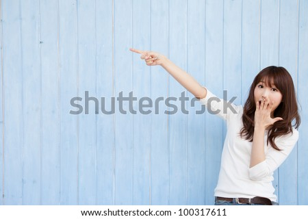 Young Asian woman pointing at a blue background