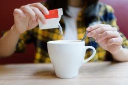Young Asian woman pouring sugar into mug.
