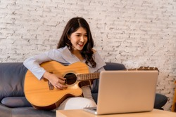 Young Asian woman practicing and learning how to play guitar on laptop computer monitor. Female guitarist watching online tutorial.