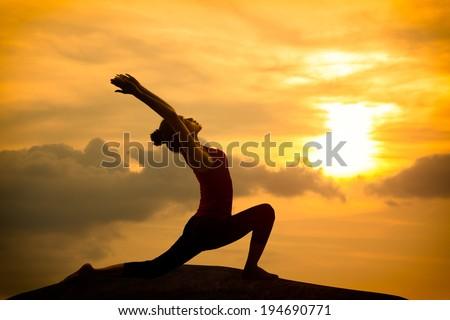 Young asian woman practicing yoga warrior pose at sunset