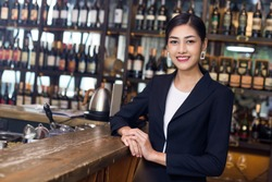 Young Asian Woman Restaurant Standing with Happy Emotion. Woman Present Wine for Customer at Bar. Woman with Wine in Bar Concept.