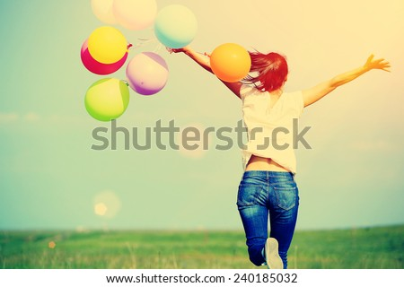 young asian woman running and jumping on green grassland with colored balloons  #240185032