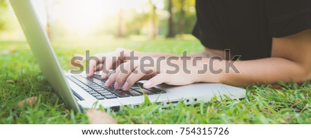 Young asian woman's legs on the green grass with open laptop. Girl's hands on keyboard. Distance learning concept. Happy hipster young asian woman working on laptop in park. Panoramic banner.