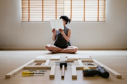 Young asian woman self assembly wooden furniture and read blank white paper to put instruction