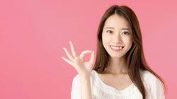 Young asian woman showing a OK hand sign.