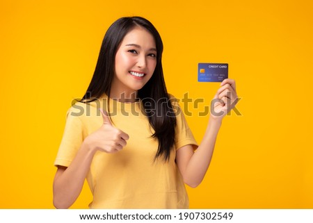 Young asian woman showing plastic credit card giving thumb up to credit card, standing over yellow background. Beautiful customer girl get satisfied of credit card service and promotion, smile face