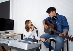 Young asian woman singing in front of electric keyboard. Her boyfriend played the guitar together. Musicians producing music in professional recording studio.