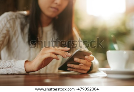 Young asian woman sitting at a table using mobile phone. Smart phone in hands of a female at outdoor cafe.