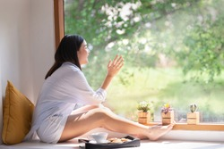 Young Asian woman sitting beside the window glass and looked out, outside of the window surrounded by green trees and morning sun