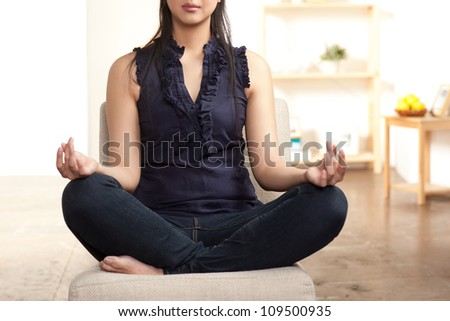 Young Asian woman sitting crossed legged in a meditation posture.