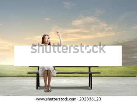 Young asian woman sitting on bench with blank banner