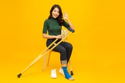 Young Asian woman sitting on chair and sprain foot using crutches and showing ok sign isolated on yellow background, Personal accident concept