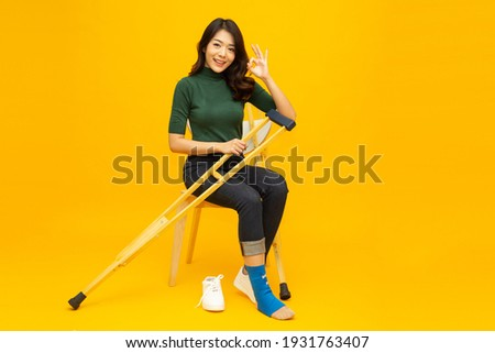 Young Asian woman sitting on chair and sprain foot using crutches and showing ok sign isolated on yellow background, Personal accident concept Сток-фото ©