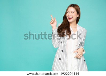 Young Asian woman smiling and pointing finger to empty copy space isolated on green background