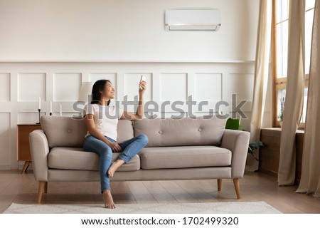 Young asian woman switching on air conditioner while resting seated on couch in modern interior living room, holds remote climate control cooler system manage temperature at contemporary home concept