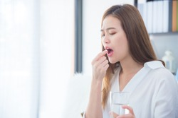 Young asian woman taking a tablet of painkiller medicine and feeling pain expression on her face .