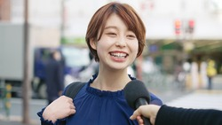 Young asian woman taking interview of TV program.