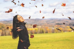 Young Asian Woman Throwing Autumn Leaves in The Air With Fall Foliage and Vermont's Green Mountains in The Background