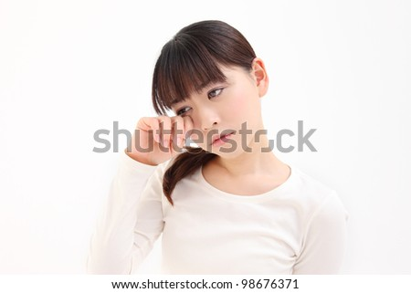 Young Asian woman touch the eye white background