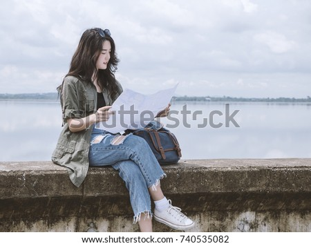Young asian woman tourist sitting and watching map beside road with copy space, beautiful backpacker tourism feeling relax in her vacation. Traveling, vacation concepts. #740535082