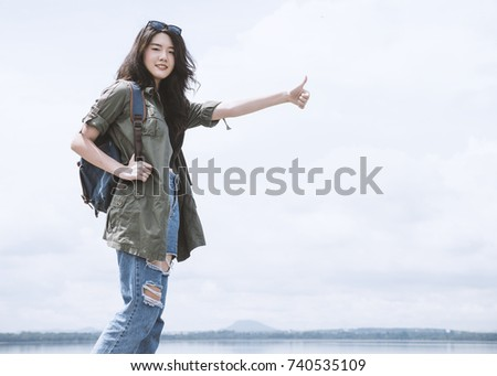 Young asian woman tourist standing and showing thumb up for need help with copy space, beautiful backpacker tourism looking at camera feeling happy in her vacation. Traveling, vacation concepts. #740535109