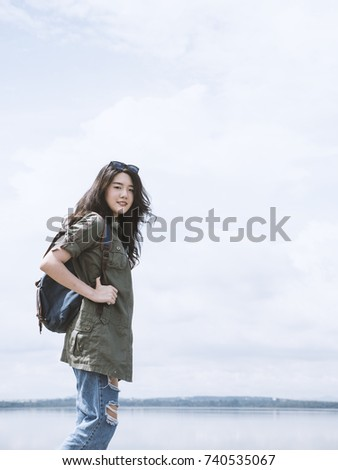 Young asian woman tourist standing with backpack and looking at camera, beautiful backpacker tourism feeling enjoy and happy in her vacation. Traveling, vacation concepts. Copy space. #740535067