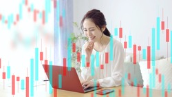 young asian woman trading using laptop with candlestick chart