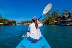 Young Asian woman traveler at Koh Chang Island, Thailand. She was kayaking to see the view of the house by the river. Travel attention on holiday. Beauty and lifestyle concept. Selective soft focus.