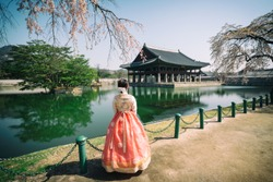 Young asian woman traveler in korean national dress or Hanbok traveling into the Gyeongbokgung Palace with cherry blossom or call sakura in spring with blue sky and clouds at Seoul city, South Korea.